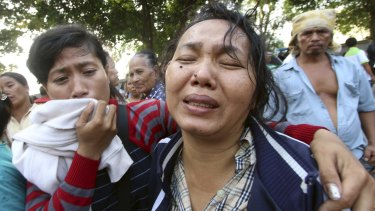 Family members cry outside at Adam Malik hospital as they wait for the bodies of victims of an Indonesian military C-130 Hercules transport plane that crashed into a residential area in the North Sumatra city of Medan, Indonesia.