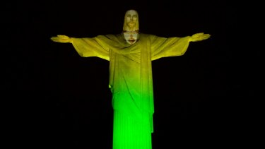 The Christ the Redeemer statue is lit in green and yellow to mark 100 days left to the Olympic Games in Rio de Janeiro, on April 27.