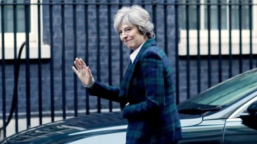 Theresa May waves as she arrives back at 10 Downing Street in London after the speech.