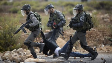 Israeli soldiers drag a wounded Palestinian man away during clashes near the occupied West Bank city of Ramallah.