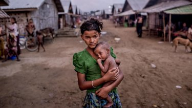 Oma Salema, 12, holds her undernourished brother, one-year-old Ayub Khan, 1, at a camp for Rohingya in Sittwe, Myanmar, this month.