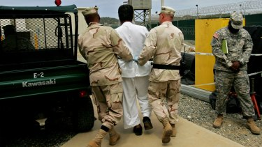 A Guantanamo detainee, centre, escorted by US military personnel at Guantanamo Bay military prison in 2007.