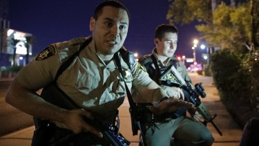 Police officers tell people to take cover near the scene of a shooting near the Mandalay Bay resort and casino on the Las Vegas Strip.