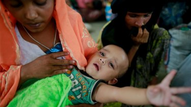 Rohingya woman Rahima, left, sits with her six-month-old child Jewel at a temporary shelter after being detained by Bangladeshi border guards while crossing the Naf River to enter Bangladesh.