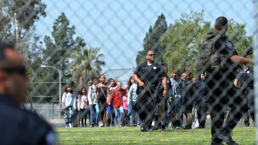 A San Bernardino police officer guides students on to the playground as multiple law enforcement agencies respond to a shooting.