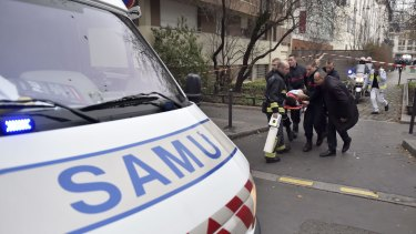 A victim is evacuated on a stretcher after armed gunmen stormed the offices of the French satirical magazine Charlie Hebdo in Paris.