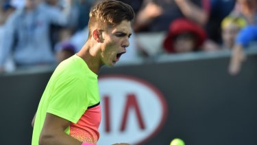 Thanasi Kokkinakis hits a return against Latvia's Ernests Gulbis.