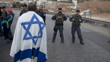 An Israeli settler draped in the country's flag stands next to Israeli police in a demonstration at the enterance to the  Palestinian village of Beit Sahur, in the occupied West Bank.