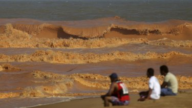 People watch the sea on the coast of Espirito Santo, Brazil, last week after mud from the tailings dam arrived 600 kilometres downstream at the Atlantic Ocean.