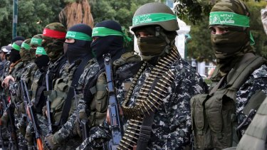 Masked militants from the Izzedine al-Qassam Brigades, a military wing of Hamas, attend the mourning ceremony for Mohammed al-Zoari, a Tunisian aviation engineer shot dead in Tunisia last year.