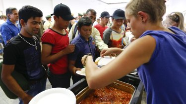 Volunteers distribute food to migrants coming from Budapest at  the train station in Munich, Germany.