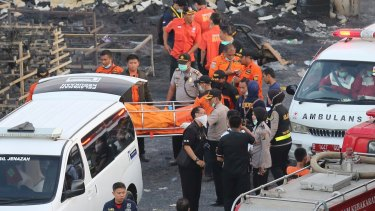 Police officers and rescuers carry a body from the scene of the fire.