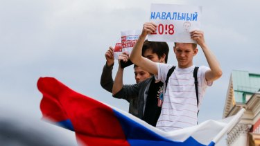 A young protester holds up a pro-Alexei Navalny banner during a demonstration in downtown Moscow.
