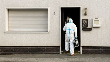 A police investigator in protective cloth enter an apartment in Wallenfels, southern Germany, where the bodies of multiple babies were found.