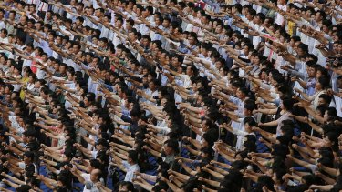 """Men and women pump their fists and chant """"Defend!"""" as they carry propaganda slogans calling for reunification of their country during the """"Pyongyang Mass Rally on the Day of the Struggle Against the US,"""" attended by approximately 100,000 North Koreans in June."""