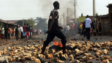A man walks past a burning tyre during protests against the governing party in Bujumbura in June.