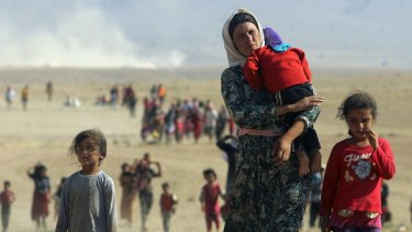 """Here displaced people from the Yazidi sect flee the Islamic State in Sinjar, Iraq. Amnesty has accused governments of """"pretending the protection of civilians is beyond their power."""""""