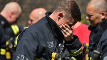 A firefighter puts looks floral tributes before a minute's silence near to Grenfell Tower on Monday.
