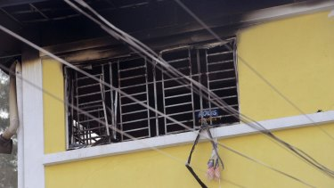 A forensic police officer investigates an Islamic religious school following a fire in Kuala Lumpur on Thursday.