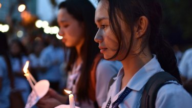 Residents offer flowers, candles, and prayers at the site of a bomb that killed more than a dozen people in Davao city, Philippines. The government blamed Abu Sayyaf for the attack.