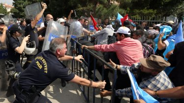 Riot police use pepper spray to push back a group of Uighur protesters trying to break through a barricade outside the Chinese Embassy in Ankara on Thursday.