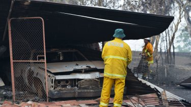 Country Fire Service volunteers work next to a burnt out shed near One Tree Hill in the Adelaide Hills on Saturday.