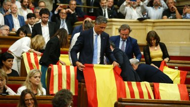 Members of the Catalan Popular Party display Spanish flags just before abandoning the session ahead of the voting during a plenary session at the Parliament of Catalonia in Barcelona.