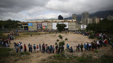 Shoppers queue outside a supermarket in Caracas.