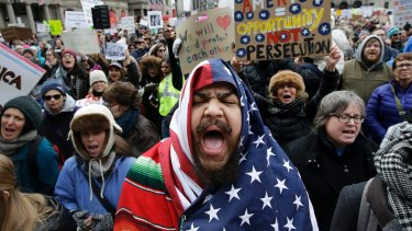 Izzy Berdan, centre, wears a US flag as he chants slogans with other demonstrators during a rally against President Donald Trump's travel in Boston.