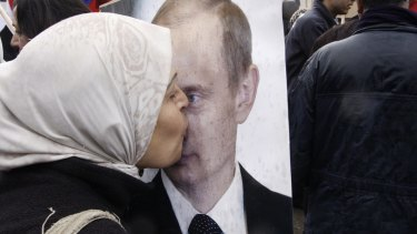 A Syrian woman kisses a poster of Vladimir Putin during a pro-Syrian government protest in front of the Russian Embassy in Damascus in 2012.