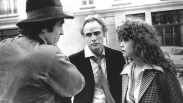 In this 1972 file photo originally provided by United Artists, Director Bernardo Bertolucci, left, Marlon Brando and Maria Schneider are shown during the filing of <em>Last Tango in Paris</em>.