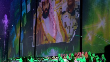 Saudi men perform under a giant screen showing an image of Saudi Crown Prince Mohammed bin Salman during National Day ceremonies last month.