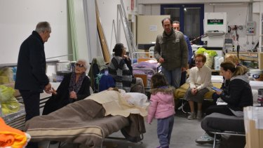 Residents prepare to spend the night in a warehouse in the village of Caldarola, Italy, on Sunday.