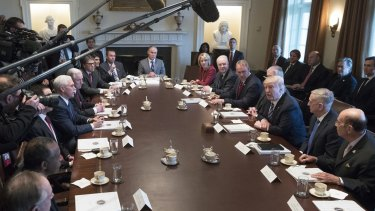 Donald Trump, centre right, with his cabinet on Monday, says it could take several years for health insurance prices to start to drop under the new plan.