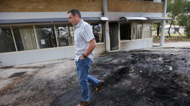 Mr Shelton examines the damage to his office after a van with gas bottles exploded in the carpark.