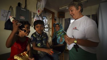Carol Nagy with Fatma, 4, Mohamed, 6, and their mother Nasma, on-board the MY Phoenix.