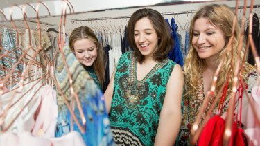 Customers pick through the racks at Dressed Up in the City, a fashion business that offers designer dress rentals.
