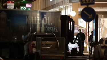 A police officer guards the scene after a truck was driven over people on a popular Swedish shopping strip.