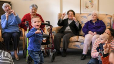 Young children and elderly residents come together to sing and dance.