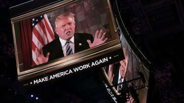 Donald Trump is seen speaking on a screen during the RNC.
