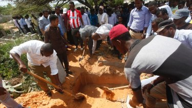 Somalis bury a victim who died in Saturday's truck blast, in Mogadishu's Medina hospital graveyard.