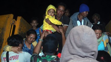 Rescuers assist villagers who were evacuated from their homes on the slope of Mount Agung.
