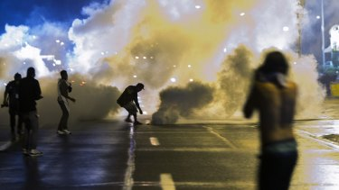 A protester throws back a smoke canister as police clear a street after a curfew imposed in the days after Michael Brown's death.