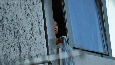 A resident peers out of a window from a small section of the building that was not on fire on Wednesday morning.