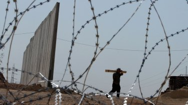 A Palestinian man walks next to a section of the wall being built near the occupied West Bank village of Masha in 2003.