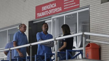 Employees stand in front an emergency entrance at the Souza Aguiar Hospital in Rio de Janeiro after the shooting.