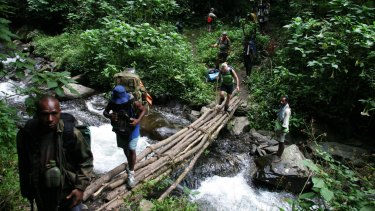 Trekkers cross the flowing river after a steep descent from the village called Alola while walking the Kokoda Track.