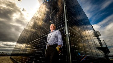 Engineering services manager Bill Burgess next to the solar panels near the top of 101 Collins.