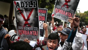Protesters hold a defaced poster of  Aung San Suu Kyi during a rally demanding justice for Rohingyas outside Myanmar's embassy in Jakarta on Friday.