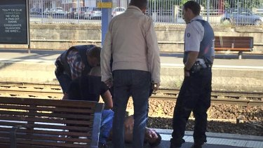 French police stand over a man who was apprehended on the platform at the Arras train station after shots were fired on the Amsterdam to Paris Thalys high-speed train where several people were injured in Arras.